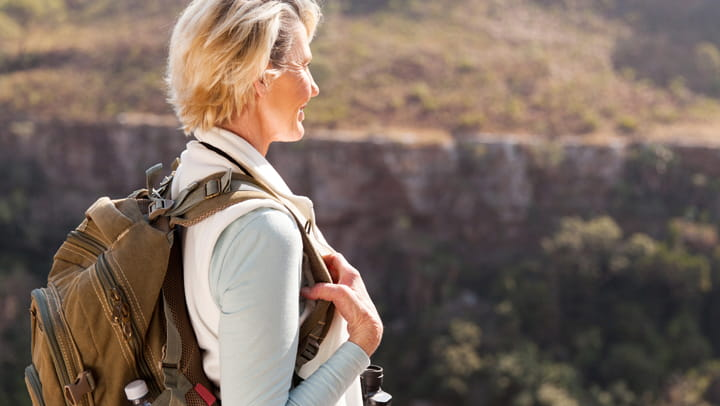 blonde woman with a backpack on looking towards the mountains