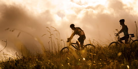 two people riding bikes in the grassy field