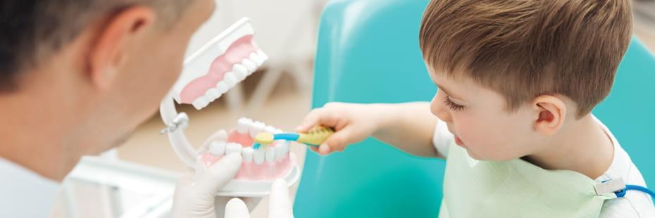 Dentist-teaching-cute-little-boy-bruching-teeth-with-toothbrush