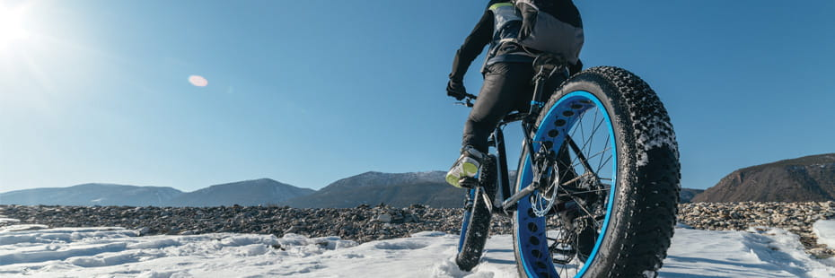 young-man-riding-fat-tire-bike-in-snowy-mountains