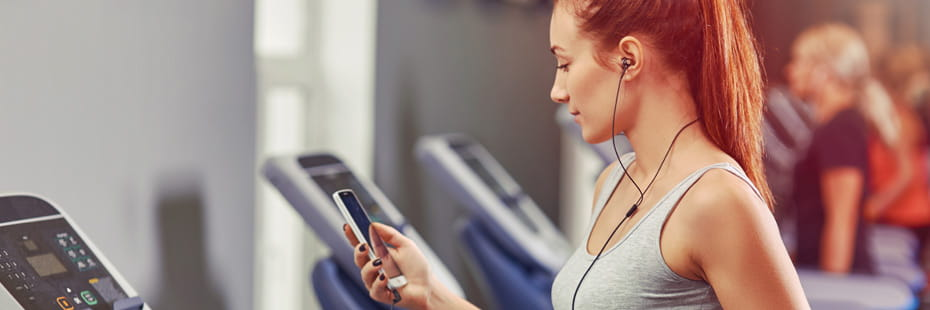 young-woman-running-on-treadmill-listening-to-music