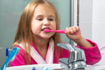 Girl-Brushing-Her-Teeth-in-the-Morning-at-Bathroom-Home