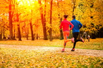 couple-running-on-path-through-park-in-fall