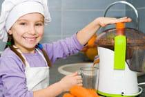 little girl juicing carrots