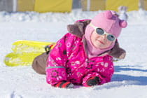 little girl laying in the snow with her skis