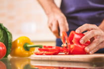 male-hand-cutting-pepper-on-cutting-board