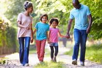 smiling-family-walking-through-park