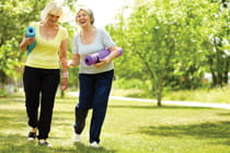 two-senior-women-walking-in-park-with-yoga-mats