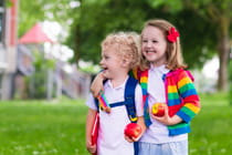two-young-children-walking-and-eating-an-apple