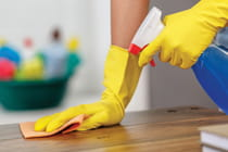 woman-cleaning-table-with-cleaning-products-in-background