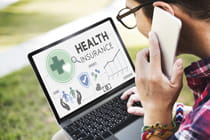 young-man-on-cell-phone-looking-at-health-insurance-online