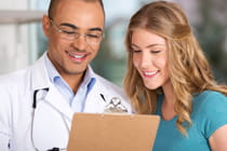 young-woman-with-doctor-reviewing-medical-information