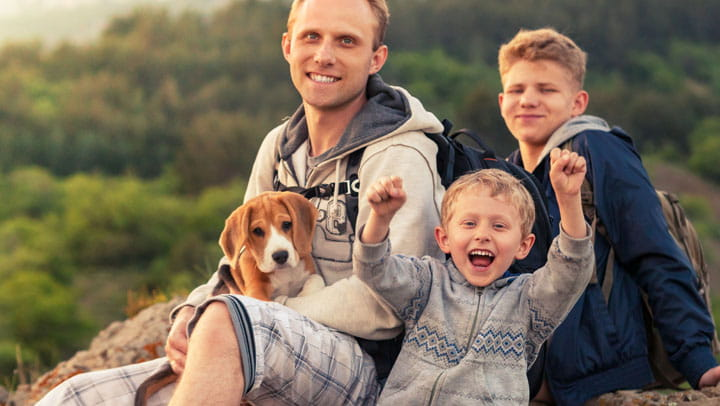 family posing on top of a mountain with puppy