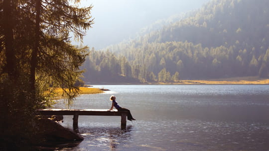 person-relaxing-on-the-dock-of-a-mountain-lake