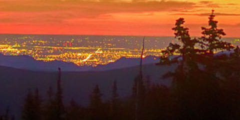 Colorado mountain sunset with city lights in background