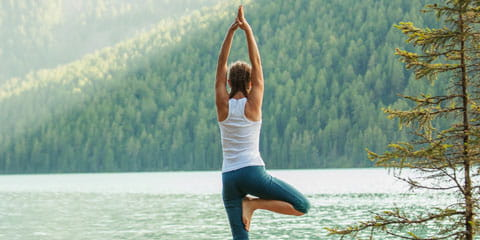 a woman doing a yoga pose on top of a rock looking forward towards the lake in the mountains