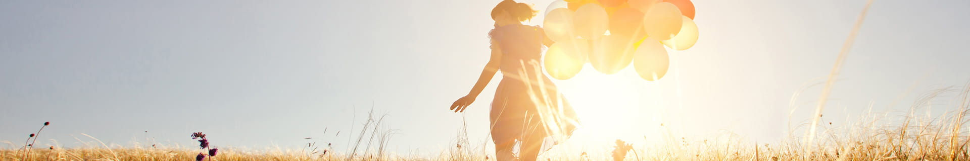 girl holding balloons in sunlight