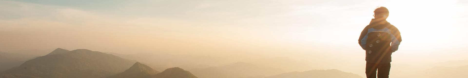 man overlooking mountain sunset